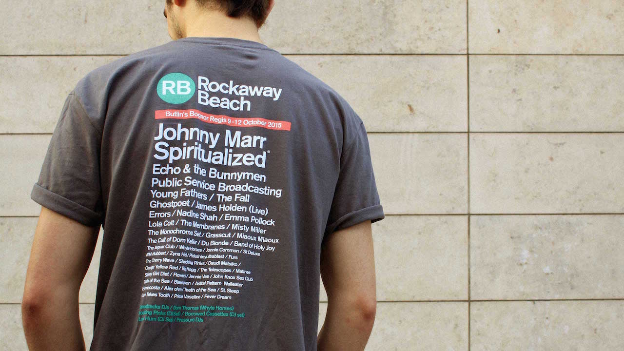 999's Mark shows off the line-up on the back of the Rockaway Beach Festival 2015 t-shirt